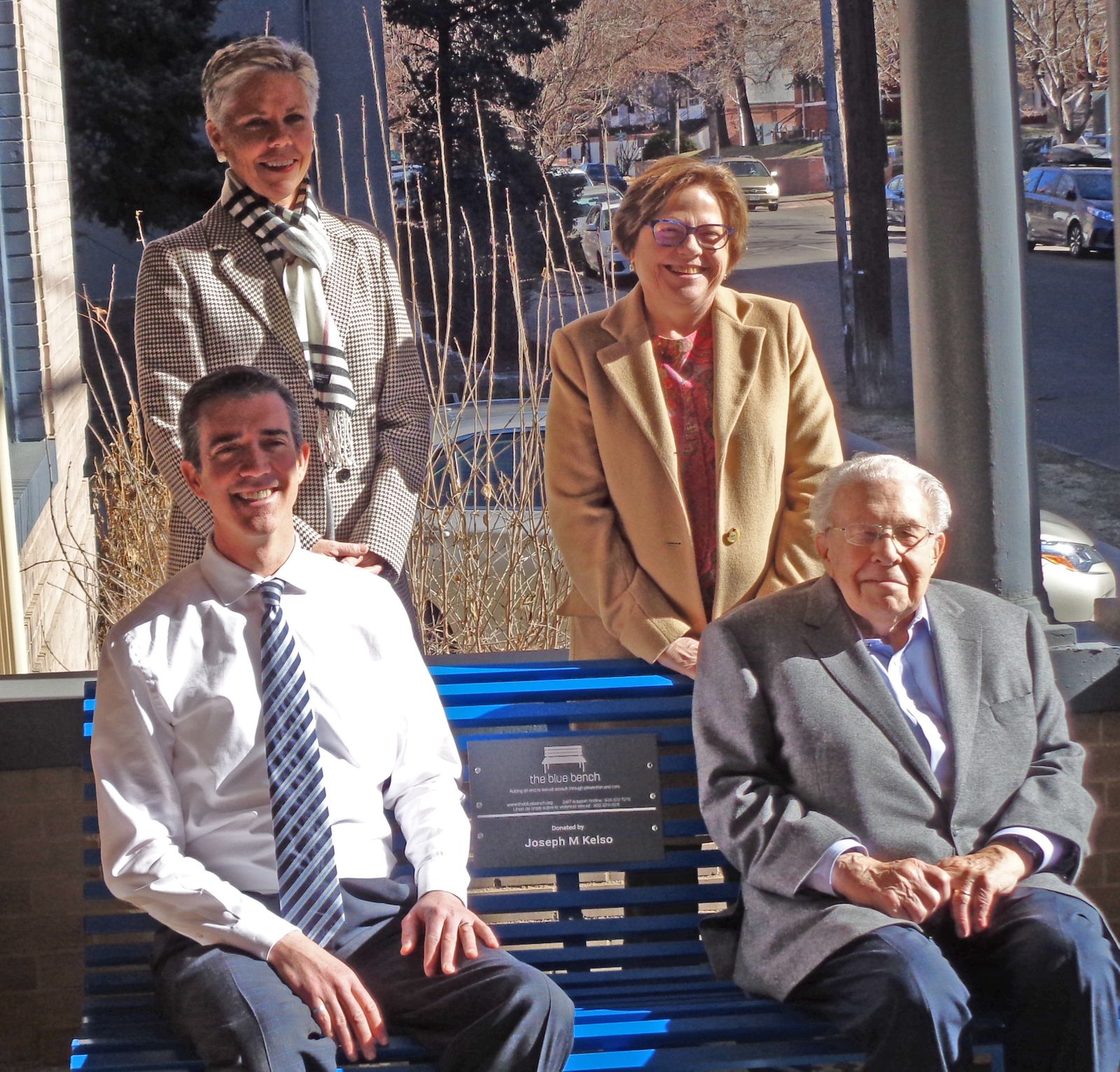 Photo of leadership members from TheBlueBench organization sitting or standing near a blue bench.