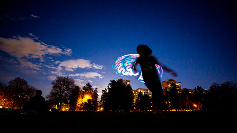 Photo at dusk of Heather Farley whips a hula hoop around her body in Cheesman park